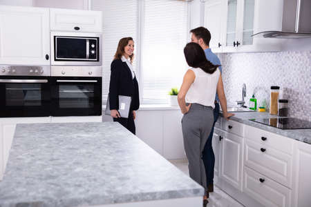 Photo pour Real Estate Agent Showing Microwave Oven In House To A Young Couple - image libre de droit