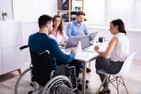 Disabled Male Manager Sitting With His Colleagues At Workplace