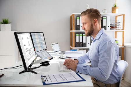 Photo pour Businessperson Calculating E-Invoice Online On Computer At Office - image libre de droit