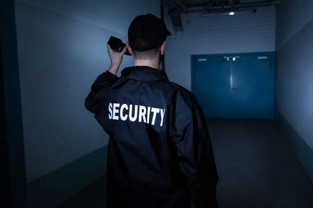 Photo for Rear View Of A Male Security Guard With Flashlight Standing In Corridor - Royalty Free Image