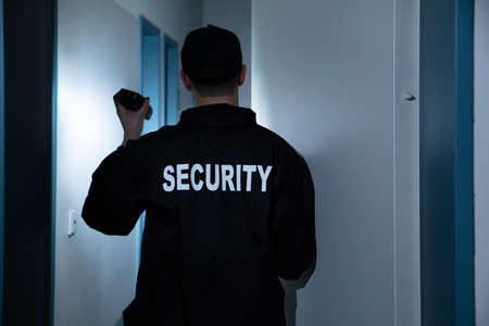 Photo for Rear View Of Male Security Guard With Flashlight Standing In Corridor Of The Building - Royalty Free Image