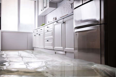 Photo pour Close-up Of Flooded Floor In Kitchen From Water Leak - image libre de droit