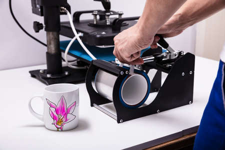 Photo pour Man printing on coffee mugs in workshop - image libre de droit