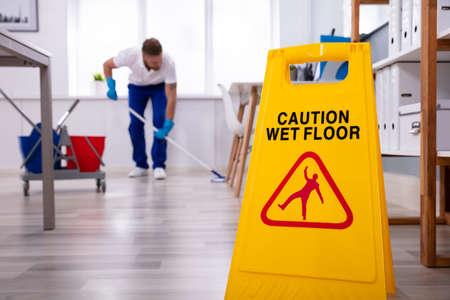 Foto de Male janitor with mop cleaning modern office floor - Imagen libre de derechos