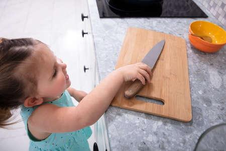 Photo pour Happy Little Baby Girl Taking Kitchen Knife - image libre de droit