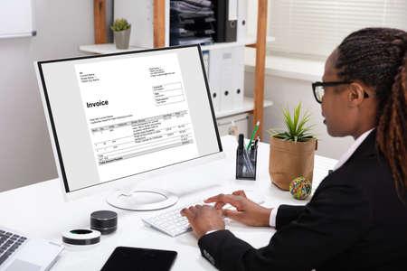 Photo pour Close-up Of A Businesswoman's Hand Checking Invoice On Laptop Over White Desk - image libre de droit