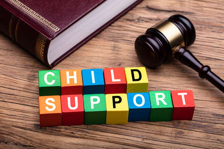 Photo pour Child Support Colorful Block With Bible And Hammer Over Wooden Desk In Courtroom - image libre de droit