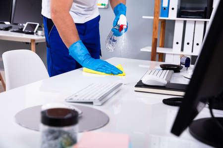 Foto de Janitor cleaning white desk in modern office - Imagen libre de derechos