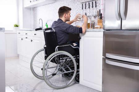 Foto de Young Disabled Man Sitting On Wheel Chair Preparing Food In Kitchen - Imagen libre de derechos