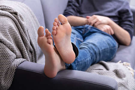 Foto de Close-up Of Man Relaxing On Sofa With His Legs Crossed In Home - Imagen libre de derechos