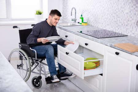 Foto de Young Happy Disabled Man Sitting On Wheelchair Arranging Plates In Drawer - Imagen libre de derechos