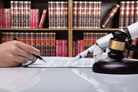 Photo pour Robotic Hand Assisting Person For Signing Document Over Reflective Desk In The Courtroom - image libre de droit