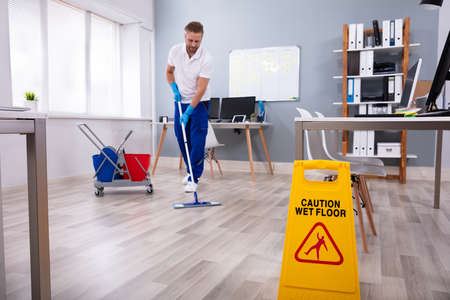 Photo pour Male janitor with mop cleaning modern office floor - image libre de droit