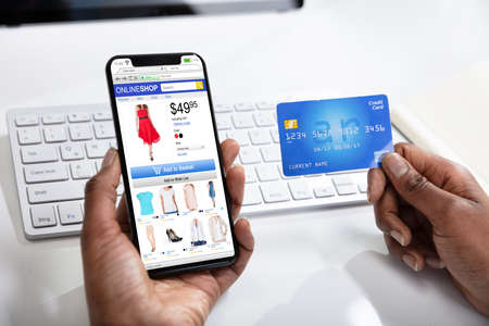 Photo pour A Woman Doing Online Shopping Using Cell Phone And Credit Card - image libre de droit