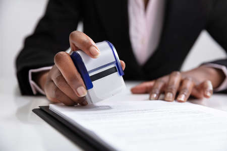 Photo pour Close-up Of Businesswoman Putting Stamp On Documents In The Office - image libre de droit