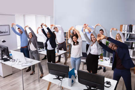 Foto de Group Of Smiling Multi-ethnic Businesspeople Doing Stretching Exercise At Workplace - Imagen libre de derechos
