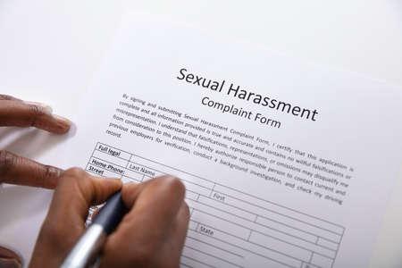 Photo pour An Elevated View Of Human Hand Filling Sexual Harassment Complaint Form With Pen - image libre de droit