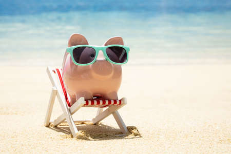 Photo pour Close-up Of Pink Piggybank With Turquoise Sunglasses On Miniature Deck Chair On Sand At Beach - image libre de droit