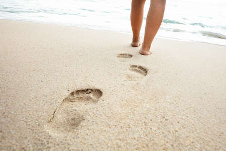Photo pour Low Section Of Woman Walking On Sand Toward Sea At Beach On Sunny Day - image libre de droit