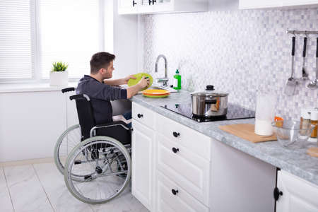 Photo pour Handicapped Man Sitting On Wheelchair Washing And Cleaning Dishes In Kitchen - image libre de droit