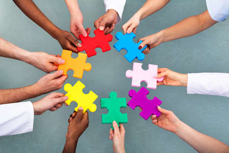 Photo pour High Angle View Of Medical Team Solving Colorful Jigsaw Puzzle Against Grey Background - image libre de droit