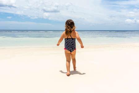 Foto de Little Girl In Bikini Walking On The Idyllic Anse Baleine Beach, Mahe Island, Seychelles - Imagen libre de derechos