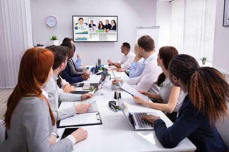 Foto de Group Of Businesspeople Having Video Conference With Another Business Team In Office - Imagen libre de derechos