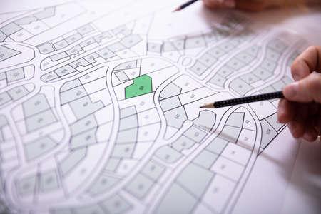 Foto de Close-up Of Human Hand Holding Pencil Over Paper Cadastre Map - Imagen libre de derechos