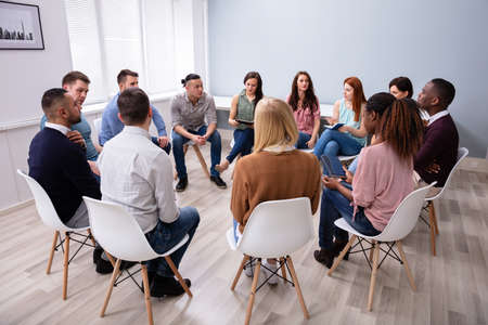 Photo pour Young Multiracial Millennial Friends Sitting In Circle Having Group Discussion - image libre de droit