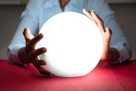 Photo pour Close-up Of Fortuneteller's Hand Covering The Glowing Crystal Ball On Red Desk - image libre de droit