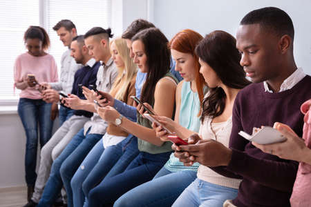 Photo pour Multi-ethnic Young People Leaning Near Table In Row Using Smartphone  - image libre de droit