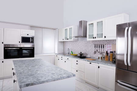 Photo for Interior Of Modern White Clean Kitchen With Microwave Oven And Refrigerator - Royalty Free Image