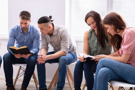 Photo pour Group Of Friend Sitting Together On Chair Reading Bible - image libre de droit