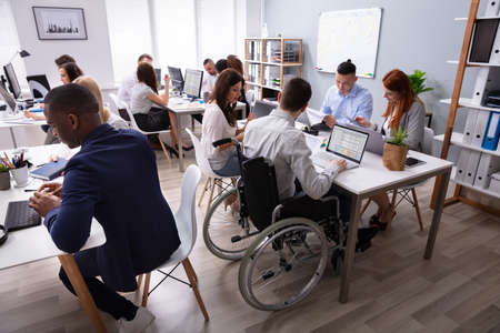 Photo pour Side View Of A Disabled Businessman Sitting On Wheelchair Using Laptop Working In Office - image libre de droit