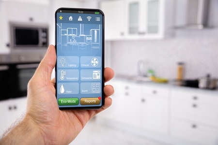 Photo pour Close-up Of Man's Hand Holding Mobile With Smart Home Control Icon Feature With Kitchen Background - image libre de droit