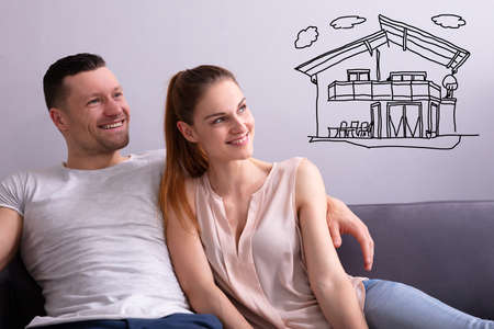 Photo pour Happy Couple Dreaming Of Having Future Home While Sitting On Sofa - image libre de droit