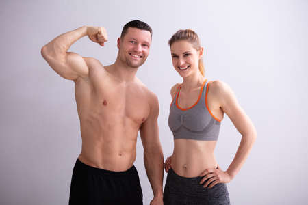Foto de Portrait Of Smiling Young Couple Showing Muscles - Imagen libre de derechos