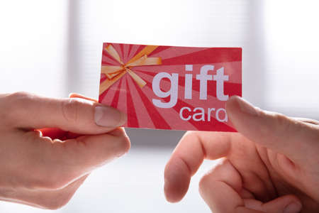 Photo pour Close-up Of Female Hand Giving Gift Card To Her Male Partner - image libre de droit
