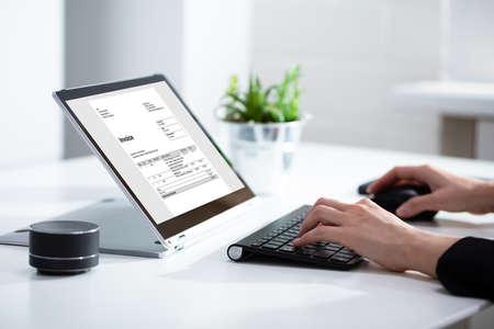 Foto de Close-up Of Businesswoman's Hands Working On Invoice On Laptop At Office - Imagen libre de derechos