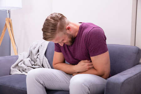 Photo pour Young Man Suffering From Stomach Pain Sitting On Sofa At Home - image libre de droit
