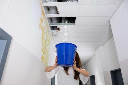 Photo pour Worried Woman Holding A Blue Bucket Under The Leak Ceiling In Corridor - image libre de droit