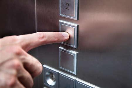 Photo pour Close-up Of Human Finger Pressing Elevator Button - image libre de droit