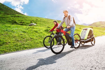 Photo pour Family With Child In Trailer Riding Mountain Bikes In Alps - image libre de droit