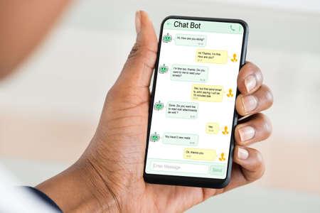 Foto de Close-up Of Woman Using Chat Bot Application For Chatting On Smartphone - Imagen libre de derechos