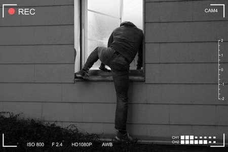 Photo pour Rear View Of A Burglar Entering In A House Through A Open Window - image libre de droit