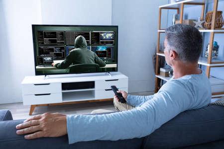 Photo pour Rear View Of Man Watching Television At Home - image libre de droit