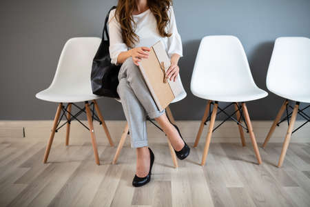 Photo pour Young Businesswoman Holding Folder While Sitting On Chair Waiting For Job Interview - image libre de droit
