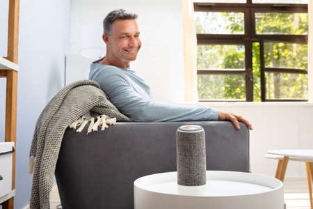 Foto de Close-up Of Wireless Speaker In Front Of Man Sitting On Sofa - Imagen libre de derechos