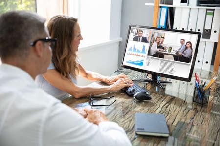 Photo pour Mature Businessman Video Conferencing With His Colleague On Computer - image libre de droit