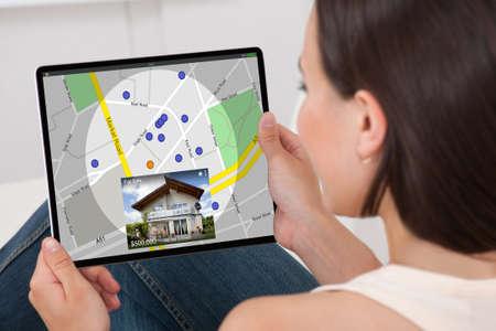 Photo pour Woman Searching For Real Estate Online On Tablet - image libre de droit